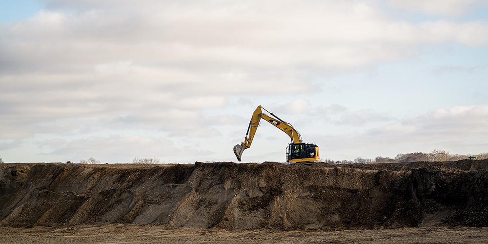 excavator on a high wall